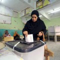 A woman casts her vote during parliamentary elections at a polling station in ,Giza